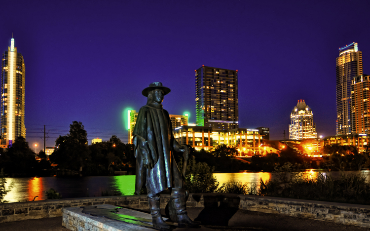 Stevie Ray Vaghan statue against the Austin skyline