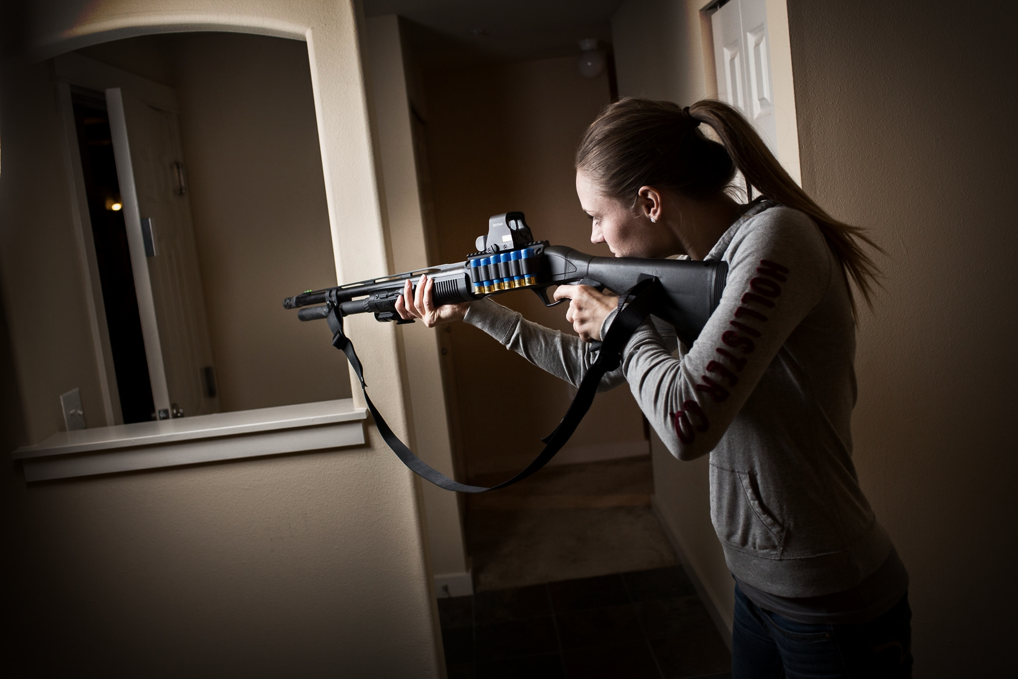 A woman holds up a shotgun