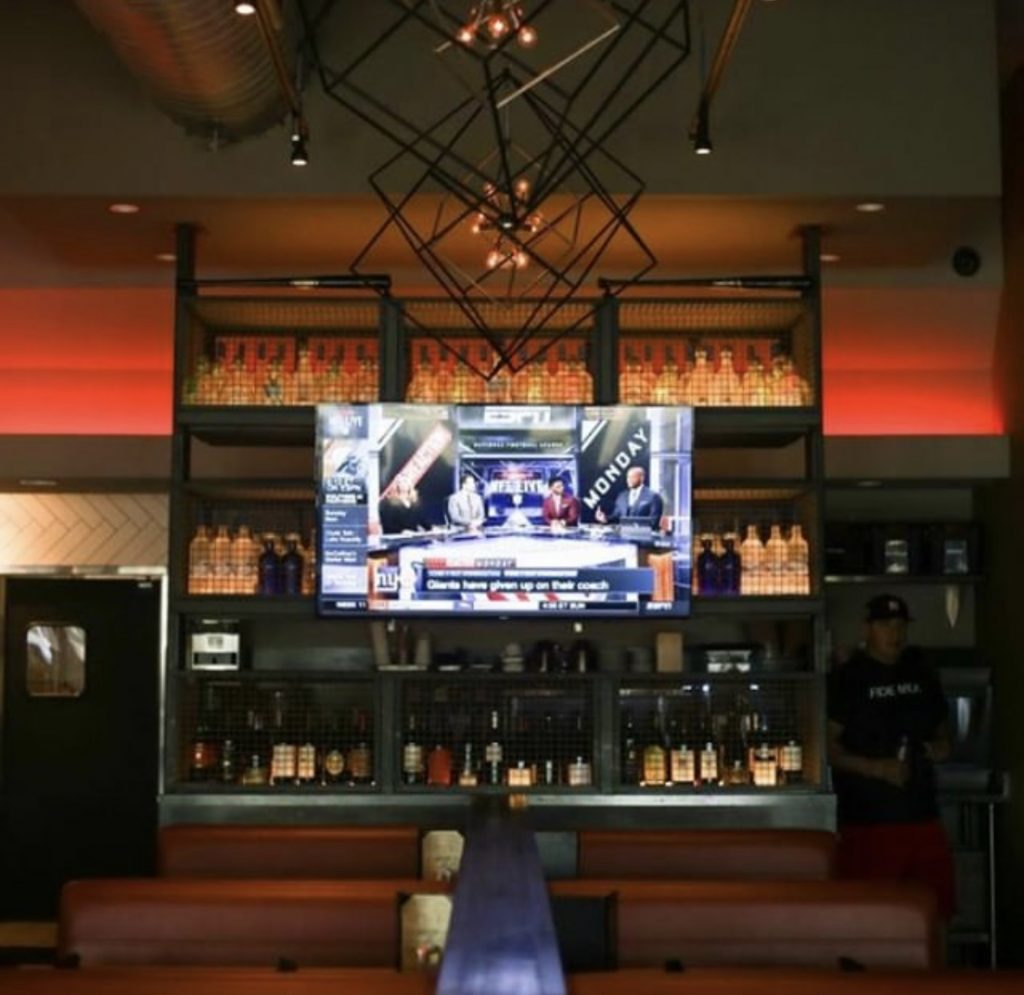 Sports commentators appear on a TV screen above  the bar at Cover 3.