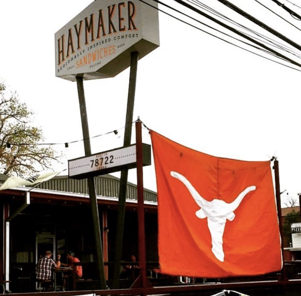 A Longhorn football flag hangs outside of Haymaker Austin.