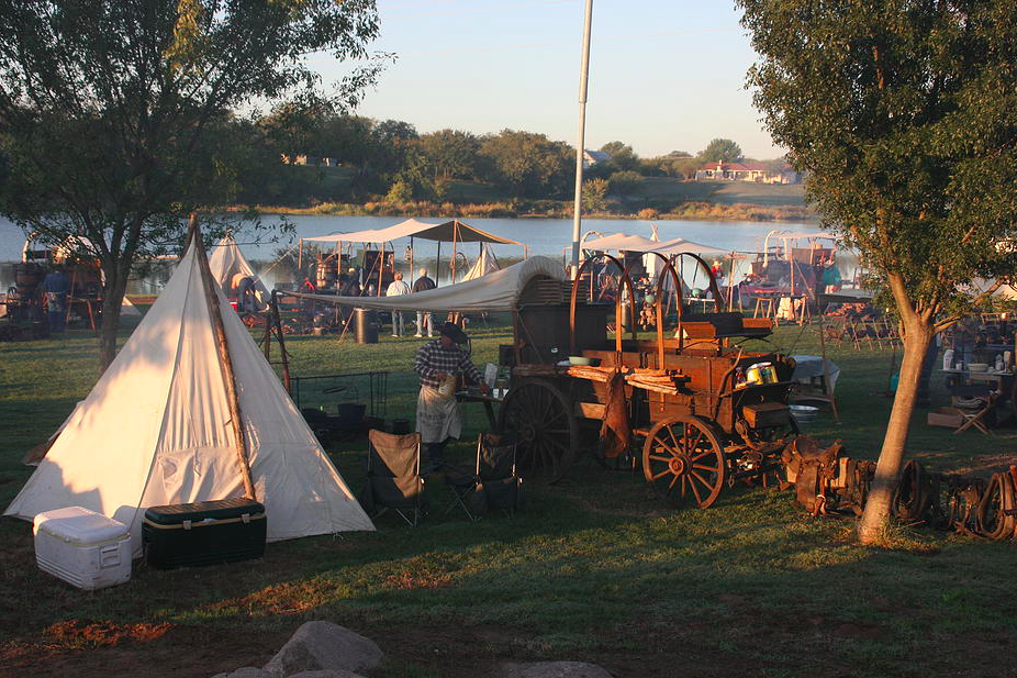 Chuck wagons and tipis line a river