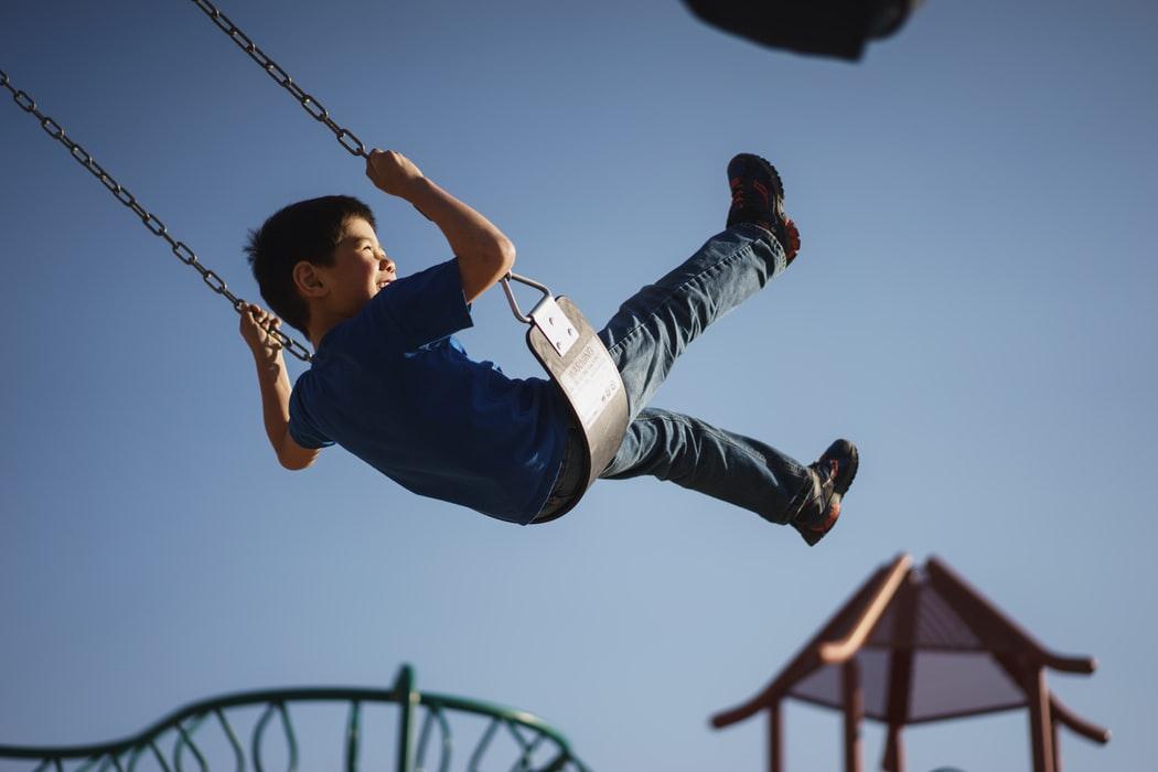 boy swinging at a playground