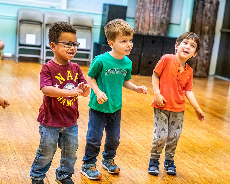 Three young boys smile and move their bodies in theatre class.